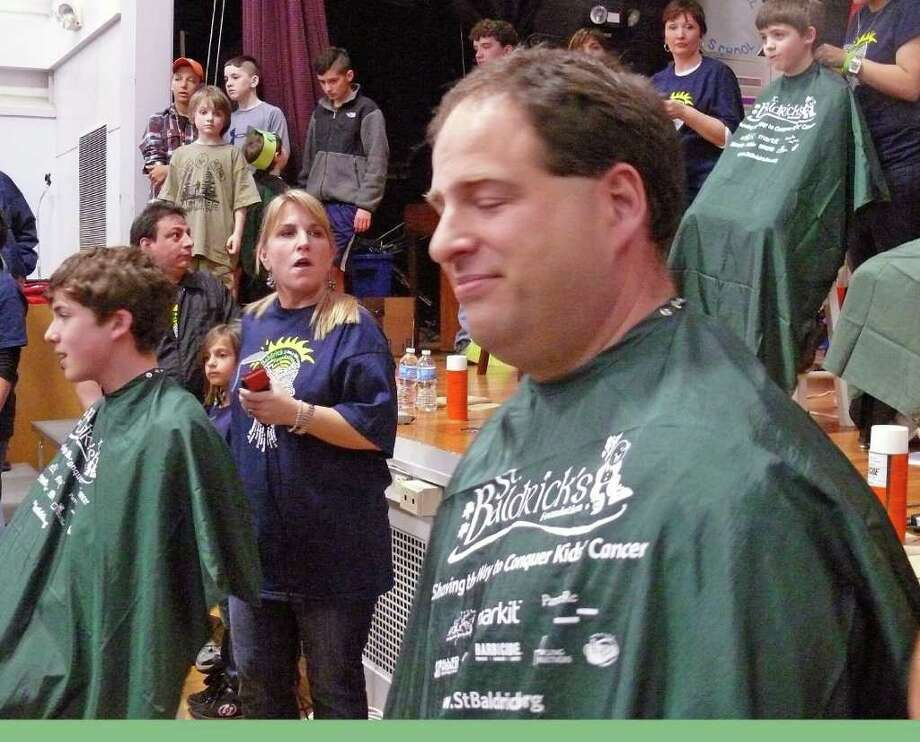 John Gerber, left, waits to get his shaved by Megan Tibball at the St. Baldrick's event held Friday at Osborn School, in memory of his younger brother, Teddy. His dad, Bill, joined him in going bald for a cause. Photo: Genevieve Reilly / Fairfield Citizen