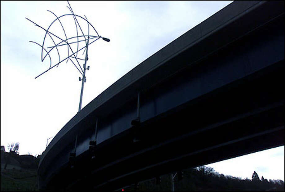 A new sculpture atop the new Galer Street Flyover southwest of Queen Anne Hill is a sort of stylized light fixture. It was paid for from the city program that uses a portion of public-works money to provide artwork. Photo: Joshua Trujillo/Seattle Post-Intelligencer