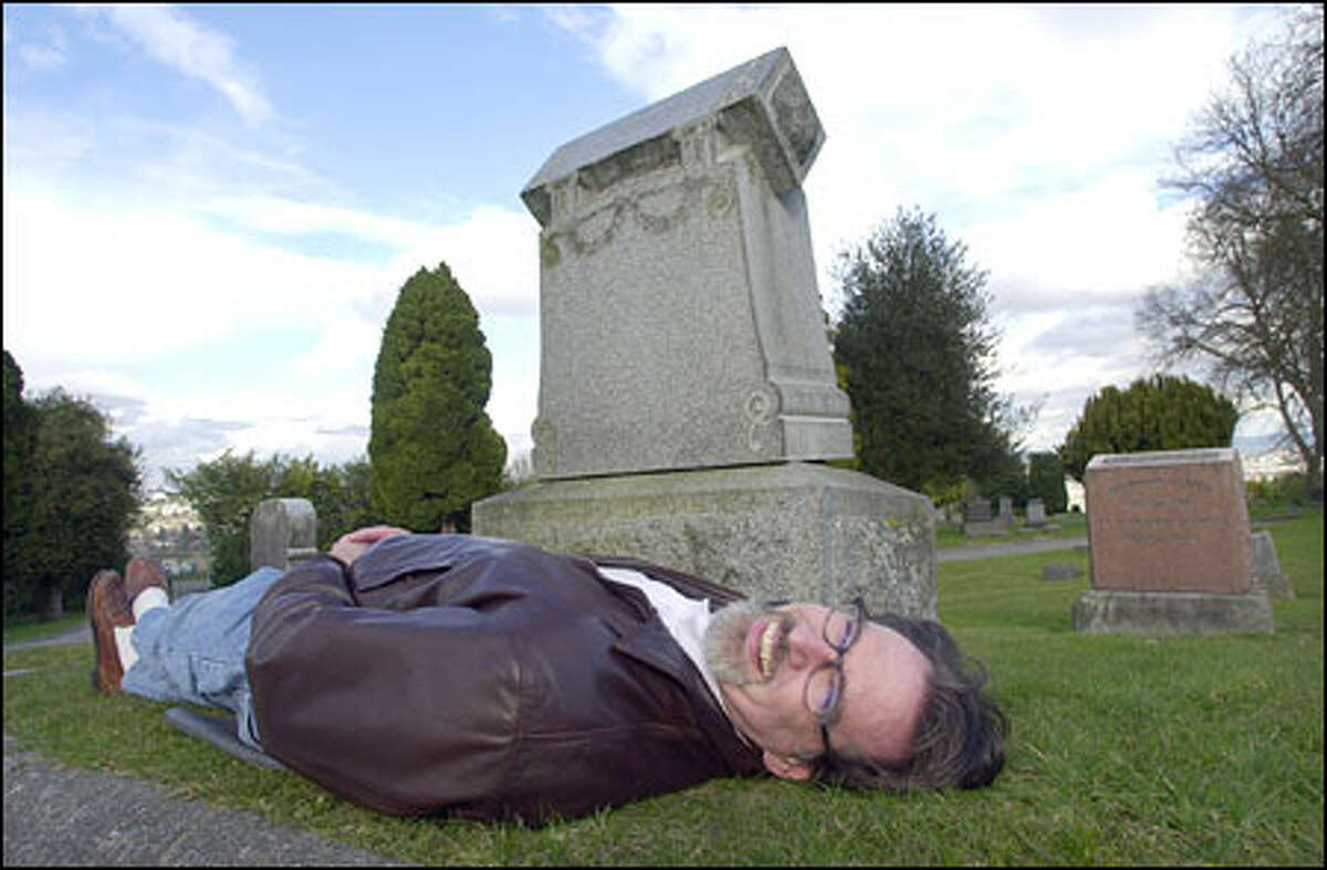 """Paul Matthaeus, CEO and chief creative officer of DigitalKitchen, poses for a photograph in front of the headstone his production house used in the opening titles for HBO's hit """"Six Feet Under"""" series in a Seattle cemetery."""