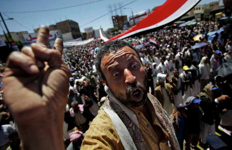 An anti-government protestor reacts during a demonstration demanding the resignation of Yemeni President Ali Abdullah Saleh, in Sanaa, Yemen, Friday, March 11, 2011. Yemen's embattled president on Thursday proposed a new constitution guaranteeing the independence of the parliament and judiciary, but thousands of unsatisfied protesters poured into the streets to demand his ouster. Opposition leaders promptly rejected President Ali Abdullah Saleh's offer and called for mass demonstrations Friday, marking a month since the protests began. (AP Photo/Muhammed Muheisen) Photo: Muhammed Muheisen / AP