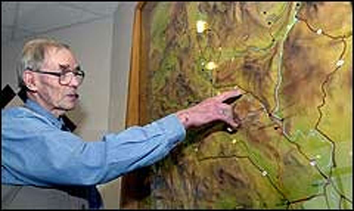 Volunteer John Brown traces the Oregon Trail on a relief map at the interpretive center. Much of the 2,170-mile trail has become too faint to find.