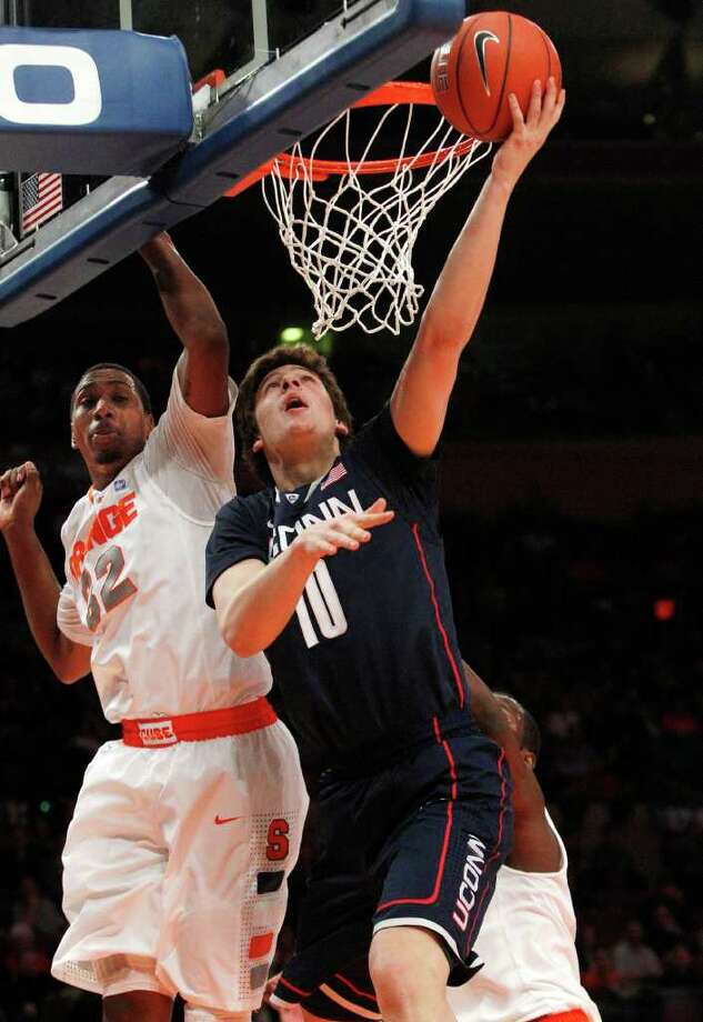 Connecticut's Tyler Olander (10) drives past Syracuse's Kris Joseph (32) during the first half of an NCAA college basketball game at the Big East Championship Friday, March 11, 2011, in New York. (AP Photo/Frank Franklin II) Photo: AP