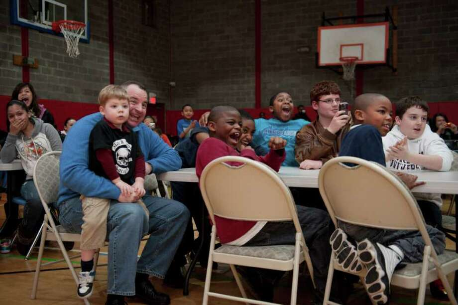 """Matthew Fahey 4, sitting on the lap of his father Dennis Fahey, Manny Axoian, Goddieu Royal 11,  Montrel Rogers 10,  Denis Fahey 13, Jhayden Soiland 8, and Brendan Fahey right react as Triple H enters the room. WWE """"Superstar"""" Paul """"Triple H"""" Levesque  talks with children at  the  Boys & Girls Club of Stamford Friday March 11, 2011 during a """"Fatherhood and Mentoring Rally"""" Triple H is also promoting his straight-to-DVD movie """"The Chaperone."""" Matthew Fahey 4sitting on the lap of his father Dennis Fahey, Manny Axoian, Goddieu Royal 11,  Montrel Rogers 10,  Denis Fahey 13, Jhayden Soiland 8, and Brendan Fahey right. Photo: Douglas Healey / Stamford Advocate Freelance"""