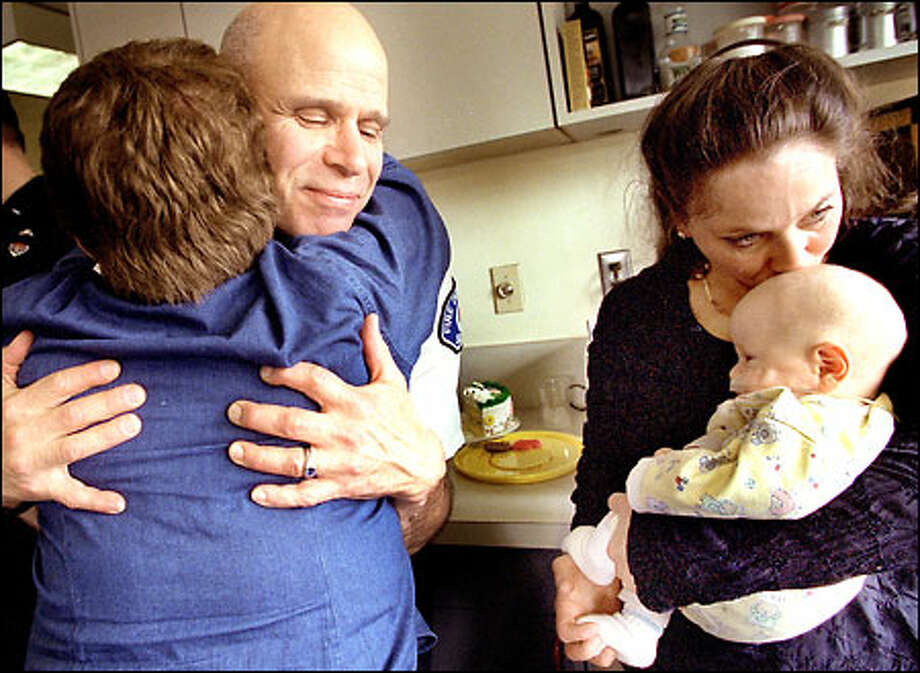 Yaakov Almoslino, 3 months, is kissed by his mother, Julia Almoslino, as paramedic Johnny Layefsky is hugged by Eva Feld, Yaakov's maternal grandmother. Photo: Renee C. Byer/Seattle Post-Intelligencer