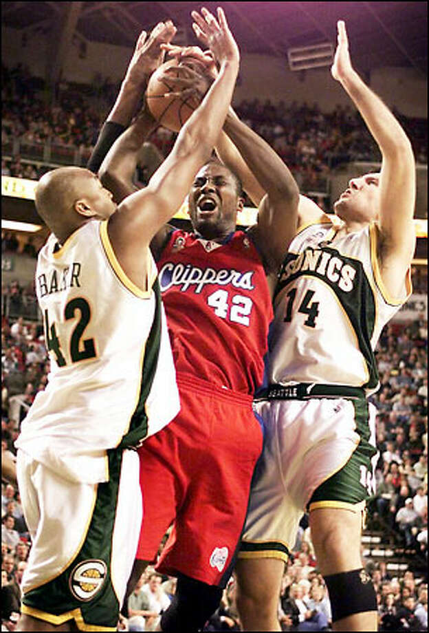 Clippers forward Elton Brand, double-teamed by Sonics defenders Vin Baker and Predrag Drobnjak, finds the paint a painful place. Photo: Mike Urban/Seattle Post-Intelligencer