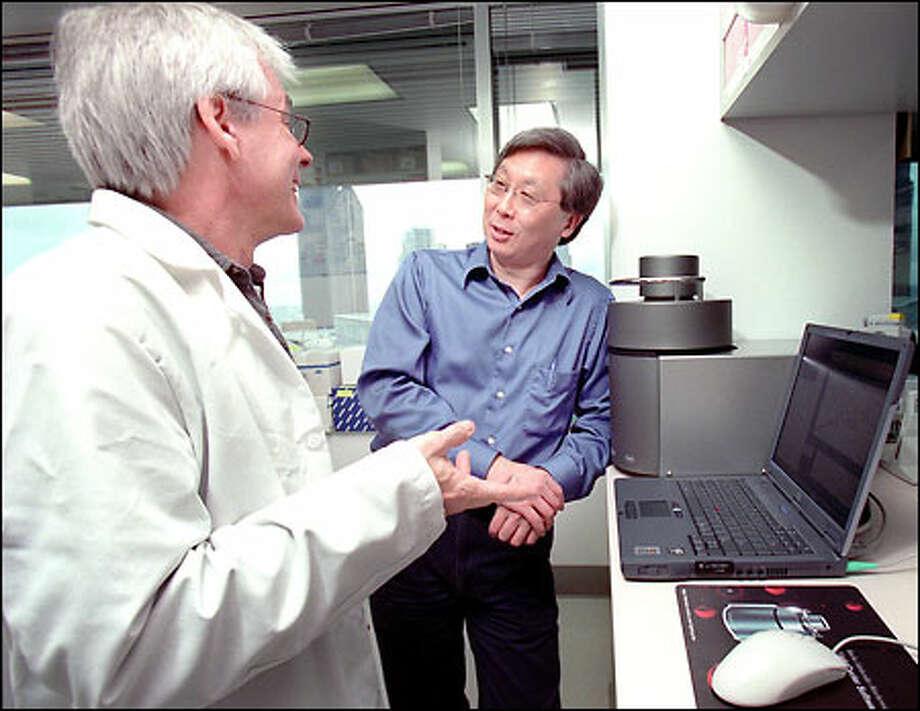 Bruce Travis, left, a scientist at International Therapeutics, talks with Glenn Kawasaki, president of the company. Kawasaki also is president of Catch Inc. Photo: Grant M. Haller/Seattle Post-Intelligencer