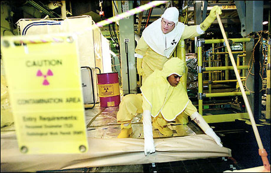 Joe Curnutt and Stephanie Green work in the K basin storage facility at Hanford, part of the massive federal cleanup of the former plutonium production site. Photo: Joshua Trujillo/Seattle Post-Intelligencer