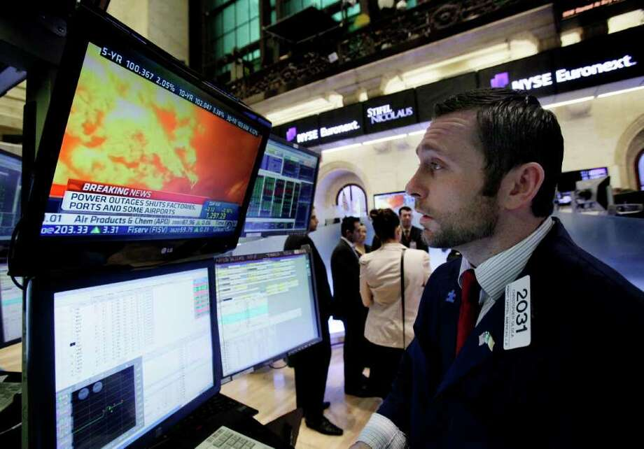 Specialist Christopher Gildea watches images from the earthquake in Japan on a television screen at his post on the floor of the New York Stock Exchange Friday, March 11, 2011. (AP Photo/Richard Drew) Photo: Richard Drew
