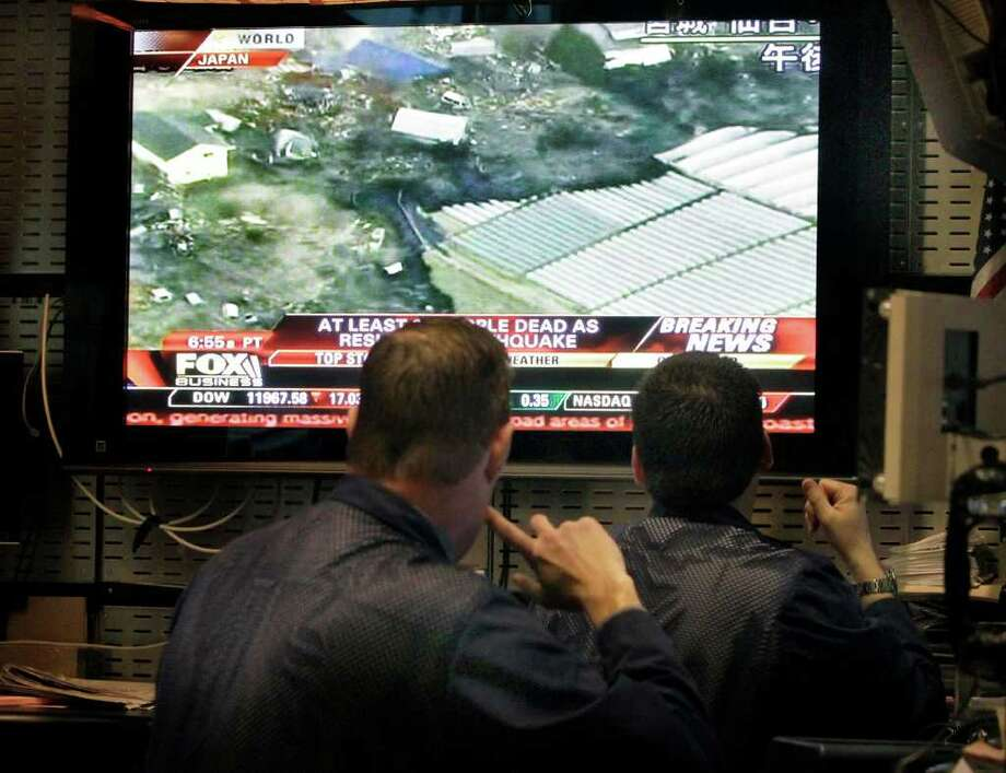 Traders watch developments of the earthquake in Japan on a television screen in their on the floor of the New York Stock Exchange Friday, March 11, 2011. (AP Photo/Richard Drew) Photo: Richard Drew