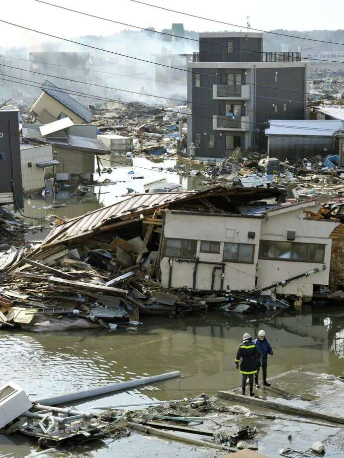 A firefighter and official check the damage of the city, caused by Saturday's earthquake and tsunami, in Kesenuma, Miyagi Prefecture, Saturday morning, March 12, 2011, after Japan's biggest recorded earthquake slammed into its eastern coast Friday. (AP Photo/Kyodo News)  MANDATORY CREDIT, NO LICENSING ALLOWED IN CHINA, HONG  KONG, JAPAN, SOUTH KOREA AND FRANCE