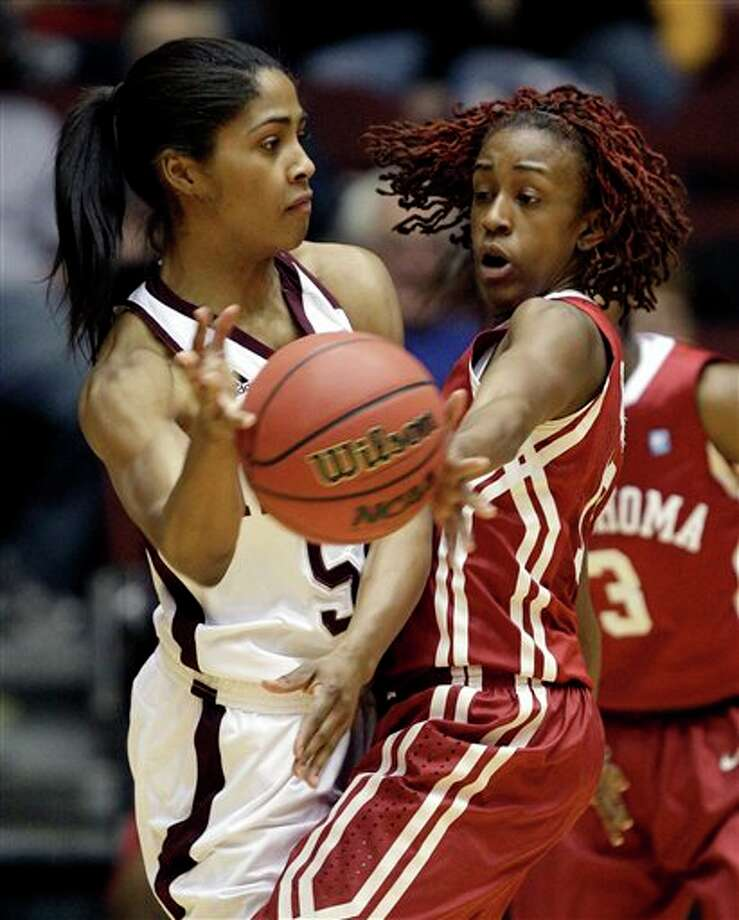 Texas A&M's Sydney Colson (left) passes around Oklahoma's Danielle Robinson. Texas A&M won 81-68 on Friday, though Robinson reached a milestone. JEFF ROBERSON/ASSOCIATED PRESS