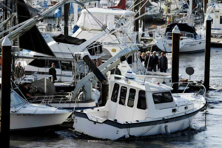A boat ripped from its anchor by a tsunami surge crashes into boats on the harbor in Santa Cruz, Cal