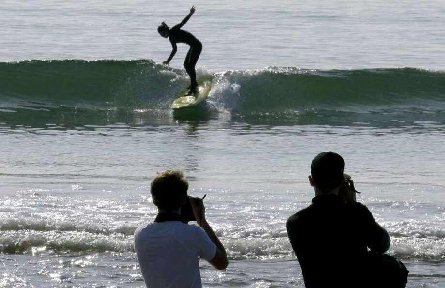 Visitors take photos as a surfer takes a wave at about the time the effects of a tsunami were expect
