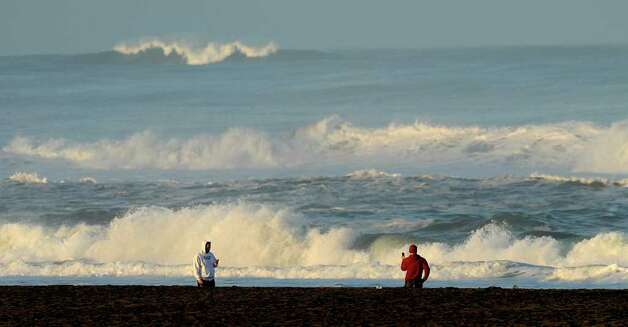 With a tsunami warning in effect for Northern California, two men watch the waves at San Francisco's Ocean Beach on Friday, March 11, 2011. The tsunami warnings came after a 8.9-magnitude earthquake struck Japan. (AP Photo/Noah Berger) Photo: Noah Berger