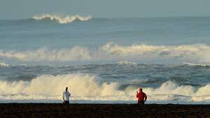 With a tsunami warning in effect for Northern California, two men watch the waves at San Francisco's Ocean Beach on Friday, March 11, 2011. The tsunami warnings came after a 8.9-magnitude earthquake struck Japan. (AP Photo/Noah Berger)