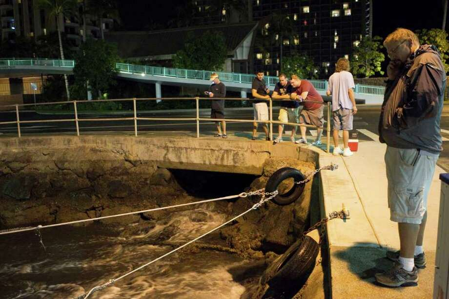 People watch the water recede from Hobron Harbor in Honolulu on Friday, March 11, 2011. Tsunami waves swamped Hawaii beaches before dawn Friday but didn't cause any major damage after devastating Japan. (AP Photo/Marco Garcia) Photo: Marco Garcia