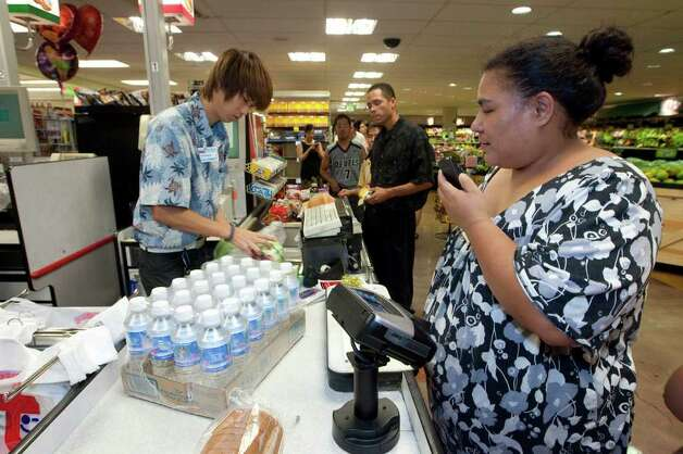 Times Supermarket employee Christopher Maeda, left, rings up water and food supplies for Charo Rodrigues Thursday, March 10, 2011 in Honolulu. The state of Hawaii is under a tsunami warning due to a large 8.9 earthquake off Japan. The earthquake is believed to have generated a tsumani wave. The Pacific Tsunami Center expects the wave to hit Hawaii at 2:59 a.m. Hawaiian Standard Time. (AP Photo/Eugene Tanner) Photo: Eugene Tanner