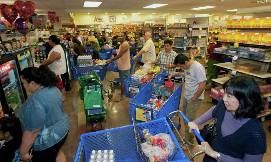 Hundreds of Oahu residents flocked to the Times Supermarket to purchase water and supplies Thursday, March 10, 2011 in Honolulu. The state of Hawaii is under a tsunami warning due to a large 8.9 earthquake off Japan. The earthquake is believed to have generated a tsumani wave. The Pacific Tsunami Center expects the wave to hit Hawaii at 2:59 a.m. Hawaiian Standard Time. (AP Photo/Eugene Tanner) Photo: Eugene Tanner