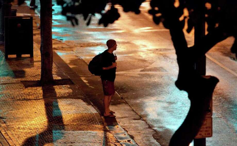 A man stands on the sidewalk on Kalakaua Avenue in Waikiki, Hawaii as a reported tsunami heads toward the Hawaiian Islands early Friday, March 11, 2011 in Honolulu. Tsunami waves hit Hawaii in the early morning hours Friday and were sweeping through the island chain after an earthquake in Japan sparked evacuations throughout the Pacific and as far as the U.S. western coast. The Pacific Tsunami Warning Center said Kauai was the first of the Hawaiian islands hit by the tsunami. Water rushed ashore in Honolulu, swamping the beach in Waikiki and surging over the break wall in the world-famous resort but stopping short of the area's high-rise hotels. (AP Photo/Eugene Tanner) Photo: Eugene Tanner