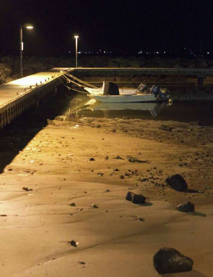 Small boats lie in the sand after water receded from Hobron Harbor in Honolulu on Friday, March 11, 2011. Tsunami waves swamped Hawaii beaches before dawn Friday but didn't cause any major damage after devastating Japan.  (AP Photo/ Marco Garcia) Photo: Marco Garcia