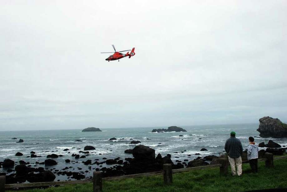 A Coast Guard helicopter flies above Pebble Beach in Crescent City, Calif. on Friday, March 11, 2011 where onlookers watch for the predicted surges of a tsunami. The first small surge was spotted at 7:38 a.m. and continued. (AP Photo/Jeff Barnard) Photo: Jeff Barnard