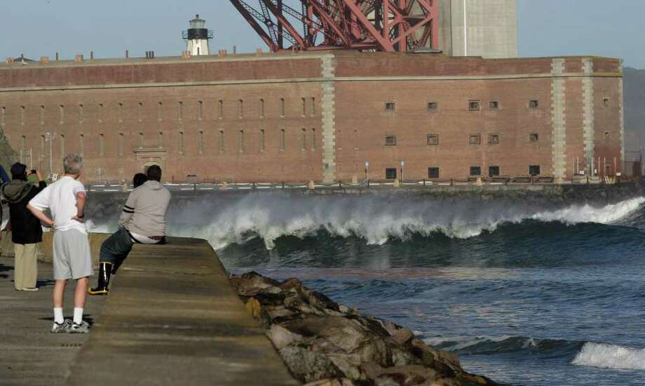 With a tsunami warning in effect for Northern California, a group of people watch as a wave hits near Fort Point under the Golden Gate Bridge in San Francisco on Friday, March 11, 2011. The warnings came after a 8.9-magnitude earthquake and tsunami struck Japan. (AP Photo/Jeff Chiu) Photo: Jeff Chiu