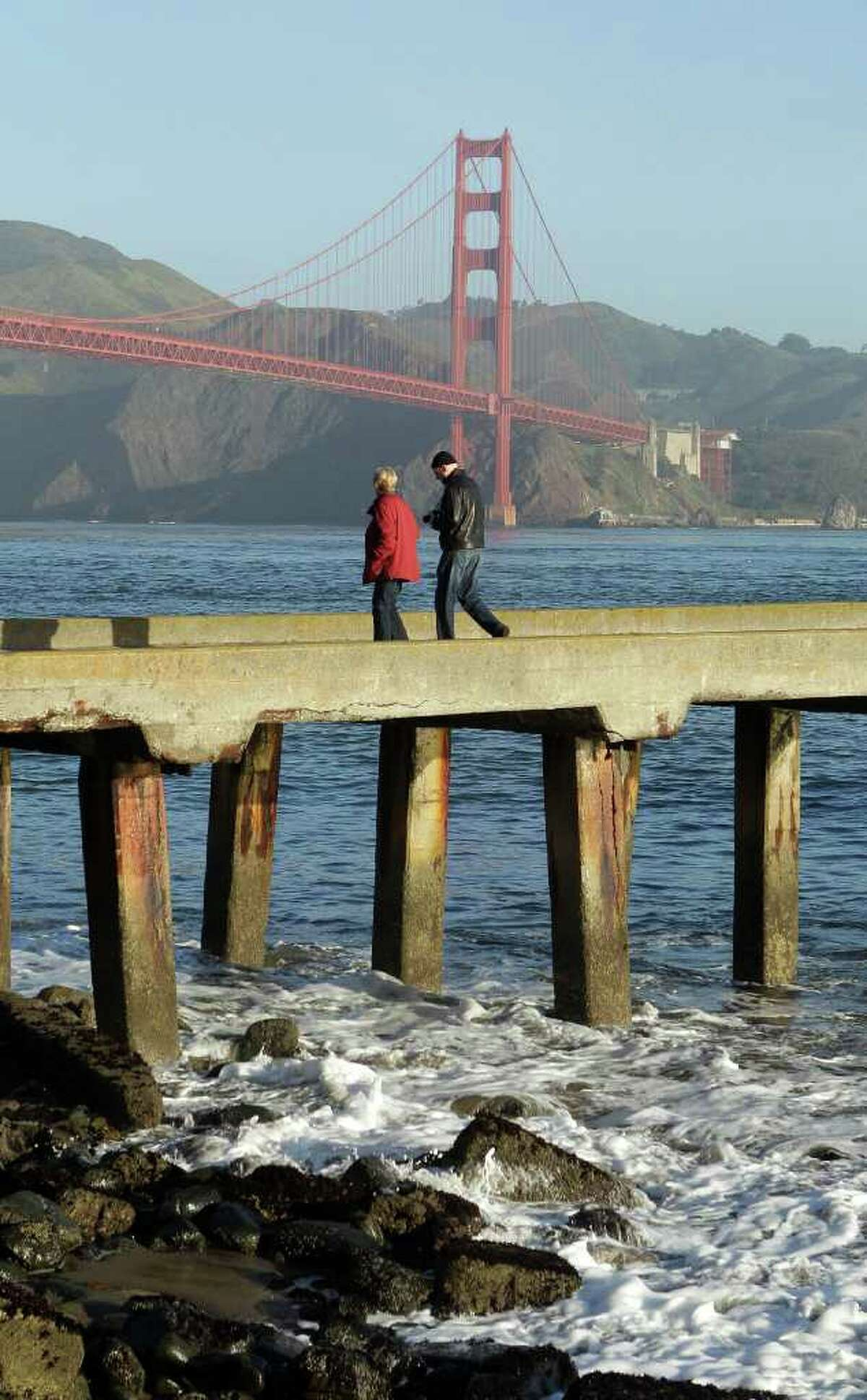With a tsunami warning in effect for Northern California, a man and woman walk along a pier at Fort Point near the Golden Gate Bridge in San Francisco on Friday, March 11, 2011. The warnings came after a 8.9-magnitude earthquake and a tsunami struck Japan. (AP Photo/Jeff Chiu)