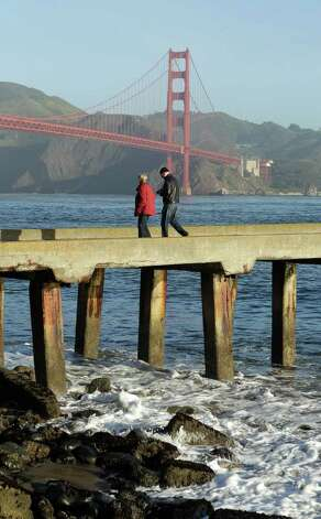 With a tsunami warning in effect for Northern California, a man and woman walk along a pier at Fort Point near the Golden Gate Bridge in San Francisco on Friday, March 11, 2011. The warnings came after a 8.9-magnitude earthquake and a tsunami struck Japan. (AP Photo/Jeff Chiu) Photo: Jeff Chiu