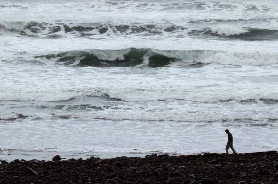 A lone person walks on the beach when a surge from a tsunami from the Japanese earthquake is expected in Seaside, Ore., Friday, March, 11, 2011. Oregon's coastal residents cleared out ahead of the first waves of a tsunami to hit the U.S. mainland, but the effects in Oregon were minor. (AP Photo/Don Ryan) Photo: Don Ryan