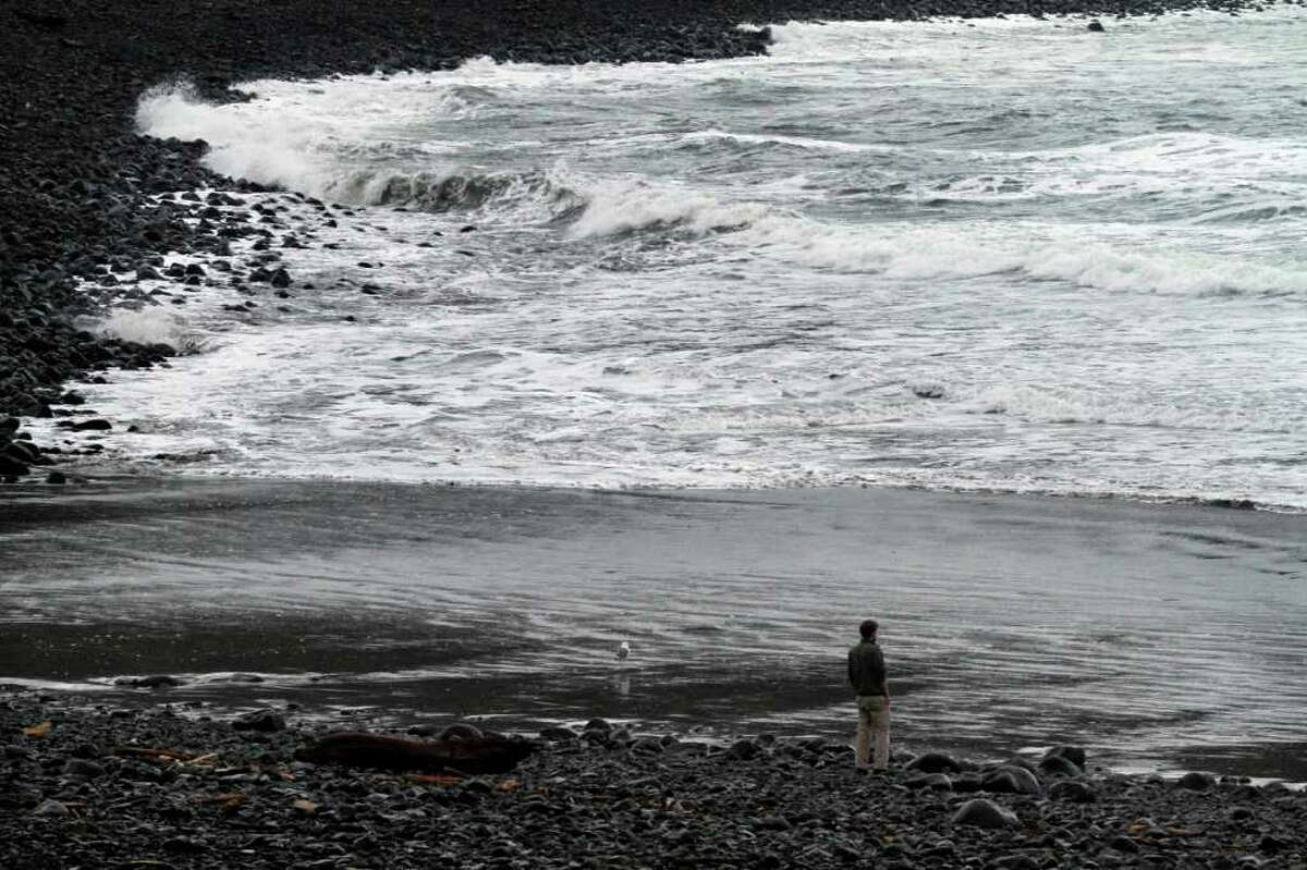 A lone person stands on the beach and watches as a surge from a tsunami from the Japanese earthquake hits the rocky coast in Seaside, Ore., Friday, March, 11, 2011. (AP Photo/Don Ryan)