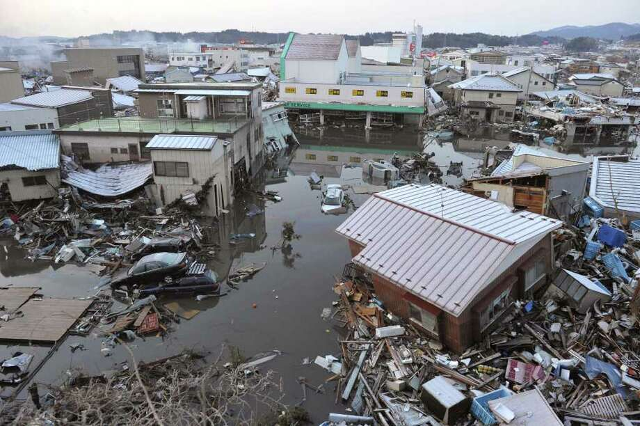 A tsunami-drifted house, bottom right, sits on the debris in Kesennuma, Miyagi Prefecture, Saturday morning, March 12, 2011 after Japan's biggest recorded earthquake slammed into its eastern coast Friday. (AP Photo/Kyodo News)  MANDATORY CREDIT, NO LICENSING ALLOWED IN CHINA, HONG  KONG, JAPAN, SOUTH KOREA AND FRANCE