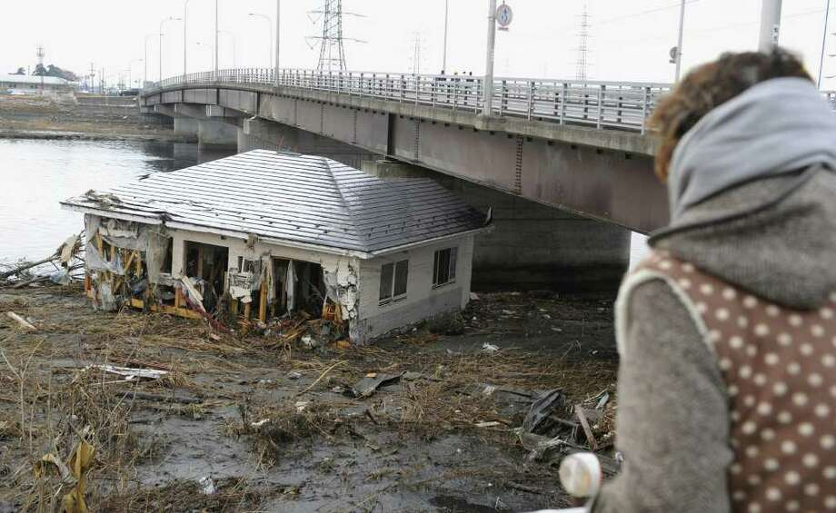 A tsunami-drifted house sits below a bridge in Sendai, Miyagi Prefecture, Saturday morning, March 12, 2011 after Japan's biggest recorded earthquake slammed into its eastern coast Friday. (AP Photo/Kyodo News)  MANDATORY CREDIT, NO LICENSING ALLOWED IN CHINA, HONG  KONG, JAPAN, SOUTH KOREA AND FRANCE