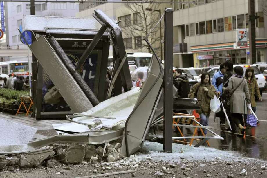 People walk past a ruined bus stop which was crushed by part of fallen outer wall of a nearby building in Sendai, Miyagi Prefecture (state) after Japan was struck by a strong earthquake off its northeastern coast Friday, March 11, 2011. (AP Photo/Kyodo News) JAPAN OUT, MANDATORY CREDIT, FOR COMMERCIAL USE ONLY IN NORTH AMERICA