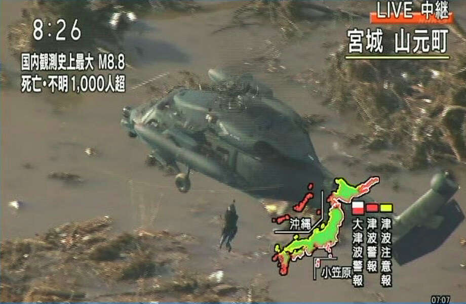 In this image made off Japan's NHK television video footrage, a crew member of Japan Ground Self-Defense Force helicopter lifts a stranded resident from the rooftop of a house in Yamamotocho, Miyagi Prefecture, northern Japan, Saturday morning, March 12, 2011, after Japan's biggest recorded earthquake slammed into its eastern coasts Friday. (AP Photo/NHK TV) MANDATORY CREDIT, JAPAN OUT, NO SALES, TV OUT, EDITORIAL USE ONLY