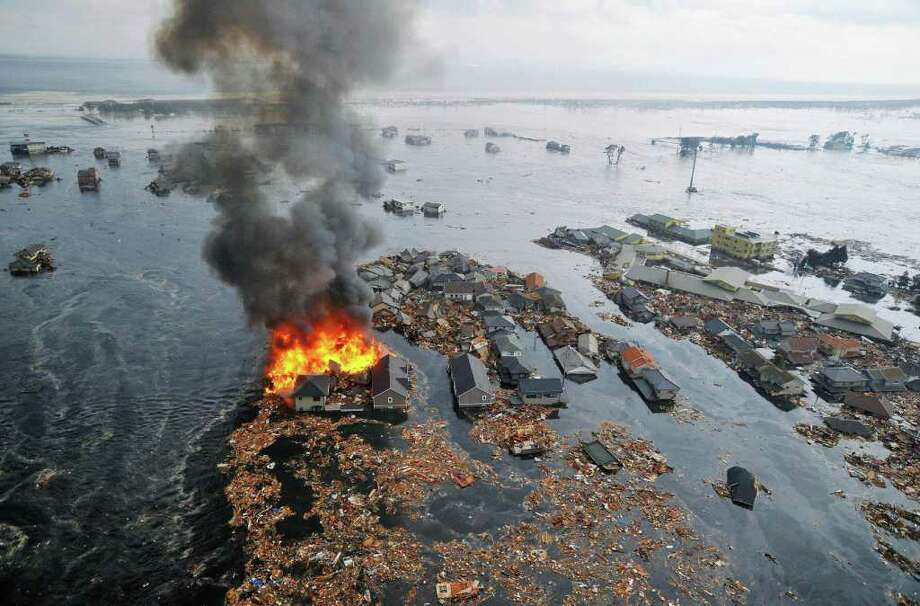 CORRECTS LOCATION - Houses swallowed by tsunami waves burn in Natori, Miyagi Prefecture (state) after Japan was struck by a strong earthquake off its northeastern coast Friday, March 11, 2011. (AP Photo/Kyodo News) MANDATORY CREDIT, NO LICENSING ALLOWED IN CHINA, HONG KONG, JAPAN, SOUTH KOREA AND FRANCE