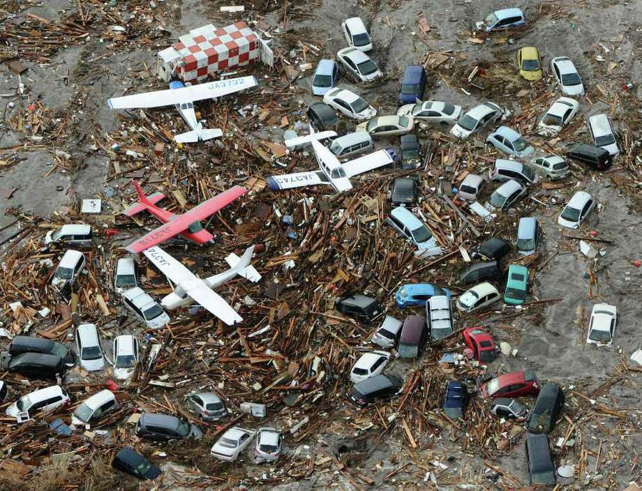 Light planes and vehicles sit among the debris after they were swept by a tsumani that struck Sendai airport in northern Japan on Friday March 11, 2022. A magnitude 8.9 earthquake slammed Japan's eastern coast Friday, unleashing a 13-foot (4-meter) tsunami that swept boats, cars, buildings and tons of debris miles inland.  (AP Photo/Kyodo News) JAPAN OUT, MANDATORY CREDIT, FOR COMMERCIAL USE ONLY IN NORTH AMERICA