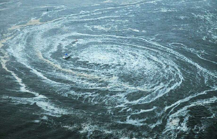 Tsunami swirls near a port in Oarai, Ibaraki Prefecture (state) after Japan was struck by a strong earthquake off its northeastern coast Friday, March 11, 2011. (AP Photo/Kyodo News) JAPAN OUT, MANDATORY CREDIT, FOR COMMERCIAL USE ONLY IN NORTH AMERICA / Kyodo News