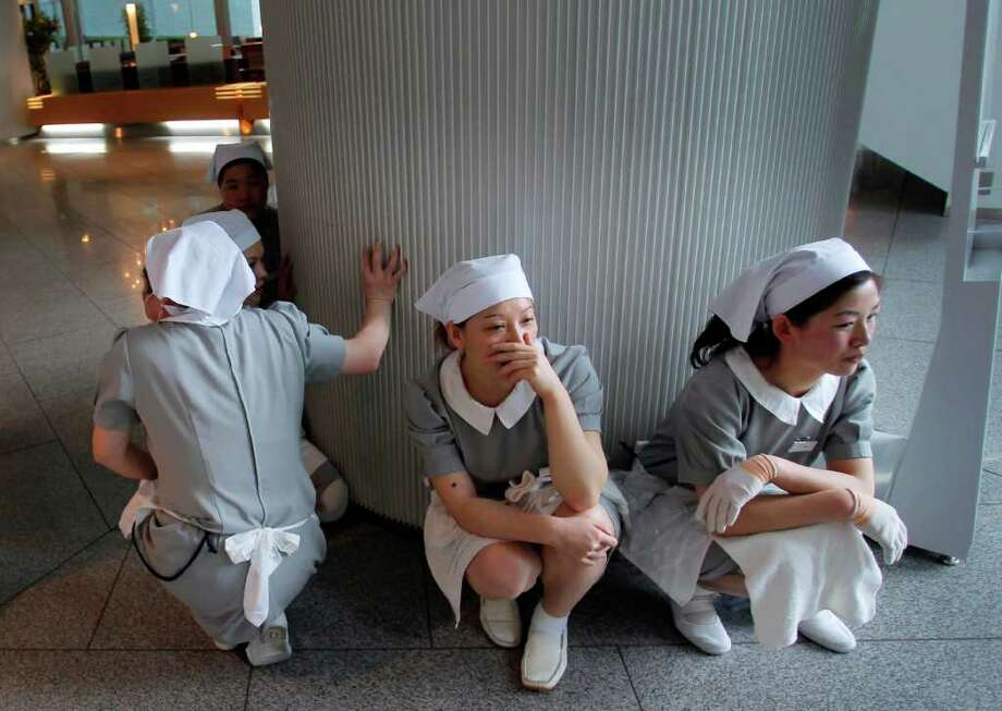 Hotel employees squat down in horror at the hotel's entrance in Tokyo after a strong earthquake hit Japan Friday, March 11, 2011. (AP Photo/Itsuo Inouye) Photo: Itsuo Inouye