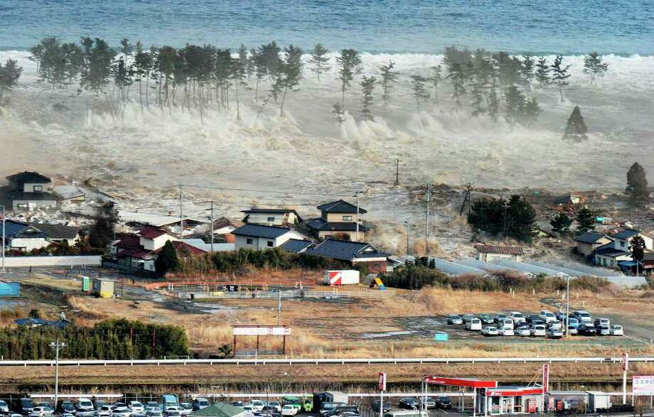 Waves of tsunami hit residences after a powerful earthquake in Natori, Miyagi prefecture (state), Japan, Friday, March 11, 2011.  The largest earthquake in Japan's recorded history slammed the eastern coast Friday. (AP Photo/Kyodo News) JAPAN OUT, MANDATORY CREDIT, FOR COMMERCIAL USE ONLY IN NORTH AMERICA