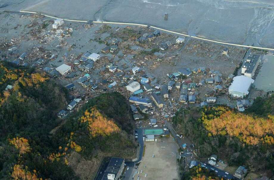 Buildings are damaged by an earthquake-triggered tsunami in Iwaki, Fukushima prefecture (state), Japan, Friday, March 11, 2011. The ferocious tsunami spawned by one of the largest earthquakes on record slammed Japan's eastern coasts. (AP Photo/Kyodo News) MANDATORY CREDIT, NO LICENSING ALLOWED IN CHINA, HONG KONG, JAPAN, SOUTH KOREA AND FRANCE