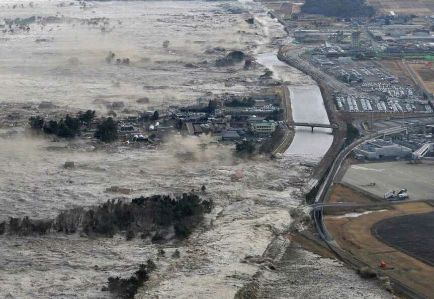 Earthquake-triggered tsunami waves sweep along Iwanuma in northern Japan on Friday March 11, 2022. T