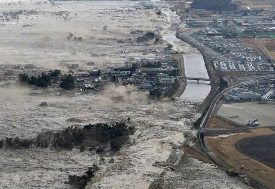 Earthquake-triggered tsunami waves sweep along Iwanuma in northern Japan on Friday March 11, 2022. The magnitude 8.9 earthquake slammed Japan's eastern coast Friday, unleashing a 13-foot (4-meter) tsunami that swept boats, cars, buildings and tons of debris miles inland. (AP Photo/Kyodo News) JAPAN OUT, MANDATORY CREDIT, FOR COMMERCIAL USE ONLY IN NORTH AMERICA, NO SALES