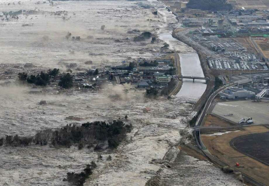 CORRECT YEAR - Earthquake-triggered tsumanis sweep shores along Iwanuma in northern Japan on Friday March 11, 2011. The magnitude 8.9 earthquake slammed Japan's eastern coast Friday, unleashing a 13-foot (4-meter) tsunami that swept boats, cars, buildings and tons of debris miles inland.  (AP Photo/Kyodo News) JAPAN OUT, MANDATORY CREDIT, FOR COMMERCIAL USE ONLY IN NORTH AMERICA