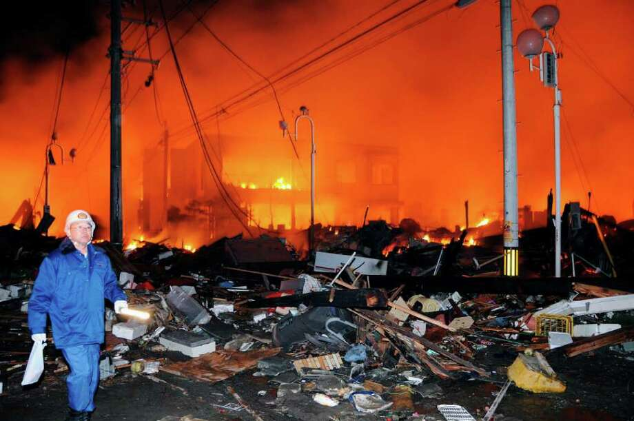 A helmeted man walks past the rubbles and a burning building after a powerful earthquake, the largest in Japan's recorded history, slammed the eastern coasts in Iwaki city, Fukushima prefecture, Japan, Friday, March 11, 2011. (AP Photo/Kyodo News) JAPAN OUT, MANDATORY CREDIT, FOR COMMERCIAL USE ONLY IN NORTH AMERICA