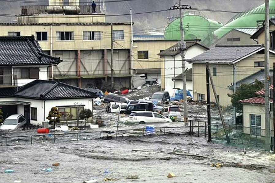 An earthquake-triggered tsunami washes away a warehouse and vehicles in Kesennuma, Miyagi prefecture