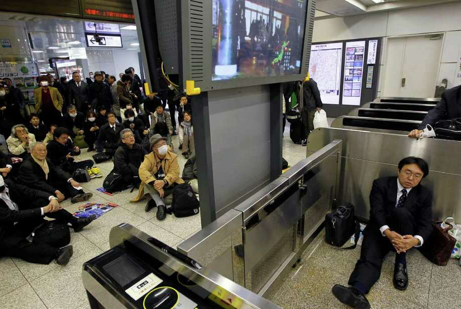 Stranded commuters watch a TV news on a powerful earthquake at Tokyo railway station as train services are suspended in Tokyo Friday, March 11, 2011. The largest earthquake in Japan's recorded history slammed the eastern coasts Friday. (AP Photo/Hiro Komae) Photo: Hiro Komae