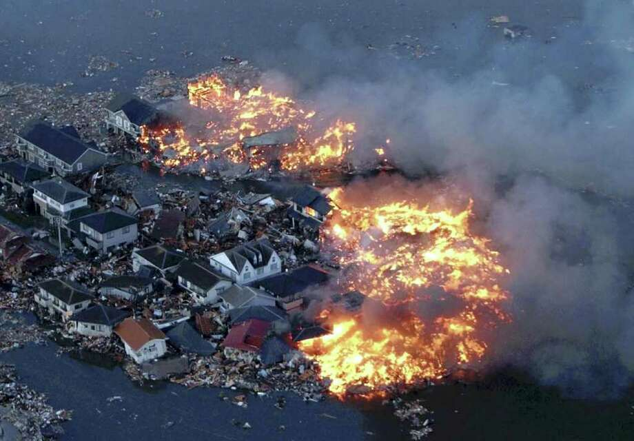 Houses are in flame while the Natori river is flooded over the surrounding area by tsunami tidal waves in Natori city, Miyagi Prefecture, northern Japan, March 11, 2011, after strong earthquakes hit the area. (AP Photo/Yasushi Kanno, The Yomiuri Shimbun)  JAPAN OUT, CREDIT MANDATORY Photo: Yasushi Kanno