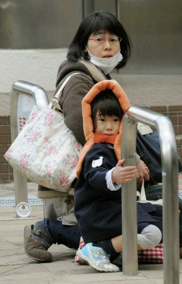 A mother and child crouch on a street in Tokyo while an earthquake hits Friday, March 11, 2011. Japan was struck by a magnitude-8.8 earthquake off its northeastern coast Friday, triggering a 13-foot (4-meter) tsunami that washed away cars and tore away buildings along the coast near the epicenter.(AP Photo/Kyodo News) MANDATORY CREDIT, NO LICENSING ALLOWED IN CHINA, HONG KONG, JAPAN, SOUTH KOREA AND FRANCE