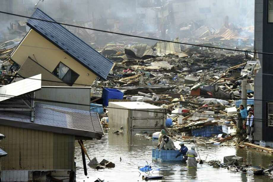 People who were left inside a building ride on a container as they are rescued in Kesennuma, northern Japan Saturday, March 12, 2011 after Japan's biggest recorded earthquake slammed into its eastern coast Friday. (AP Photo/Kyodo News)  MANDATORY CREDIT, NO LICENSING ALLOWED IN CHINA, HONG  KONG, JAPAN, SOUTH KOREA AND FRANCE