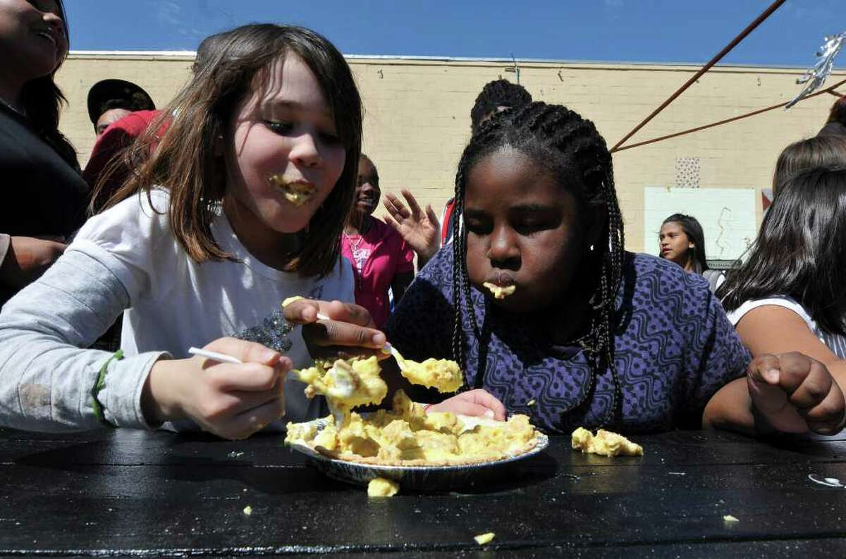 Angelina Longoria (left) and Iris Cooper take part in the pie-eating contest during Pi Day festivities Friday at the San Antonio School for Inquiry and Creativity. Pi Day is observed March 14 (which this year falls during Spring Break) in honor of the mathematical constant pi, often rounded down to 3.14.